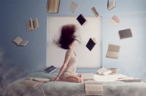 Op Onlybyme verschijnen veel boekrecensies. Deze blog geeft inzage in boekenrecensies die veel gelezen worden. De top 10 van 2018 en meer. Afbeelding toont vrouw op bed met boeken die om haar hoofd heen vliegen, kortom bewerkte foto.#top10 #boekrecensies #veelgelezen