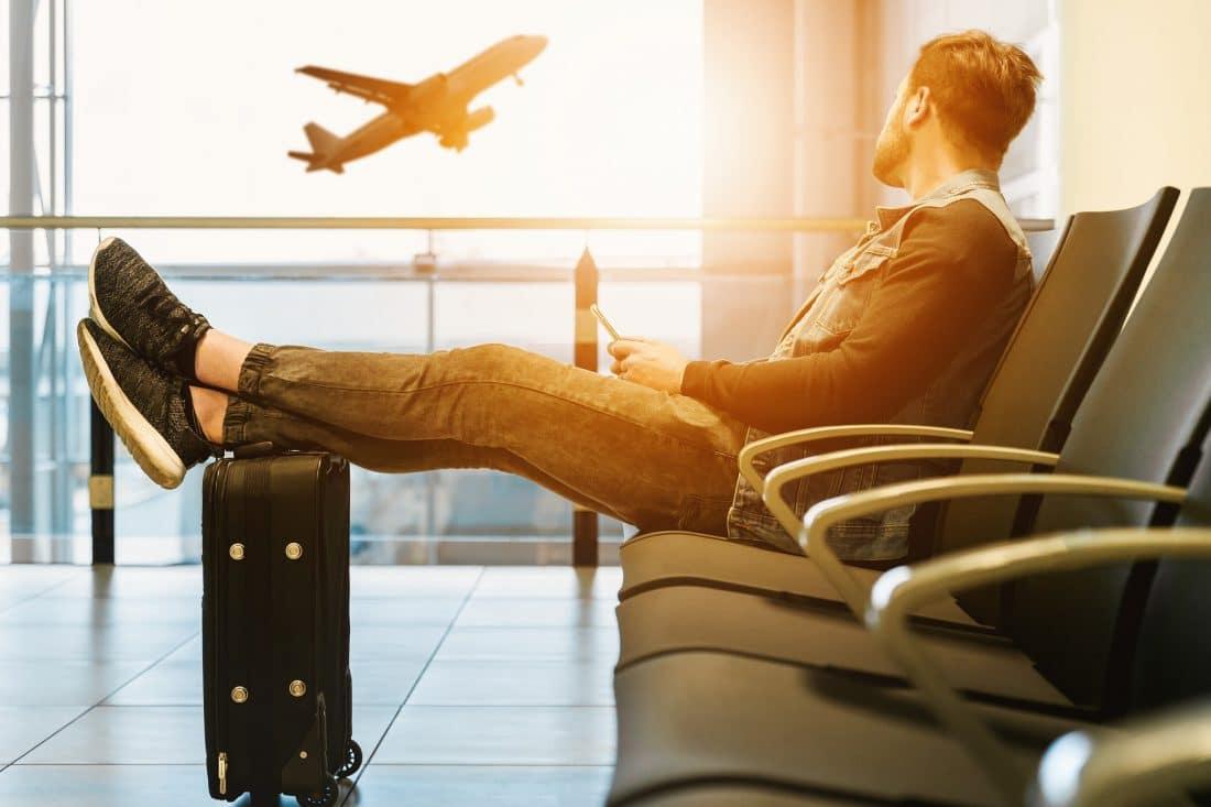 Vlucht geannuleerd? Vaak heb je recht op compensatie. Deze blog bevat informatie over het recht op vergoeding bij annulering van je vlucht en dan met name over wanneer je recht hebt op vergoeding en op welke soort vergoeding.Afbeelding toont man op stoel op luchthaven met koffer en door het raam een opstijgend vliegtuig.#compensatie #vlucht #vliegreis #rechtopcompensatie #annuleringvlucht #rechtenpassagiers #informatief